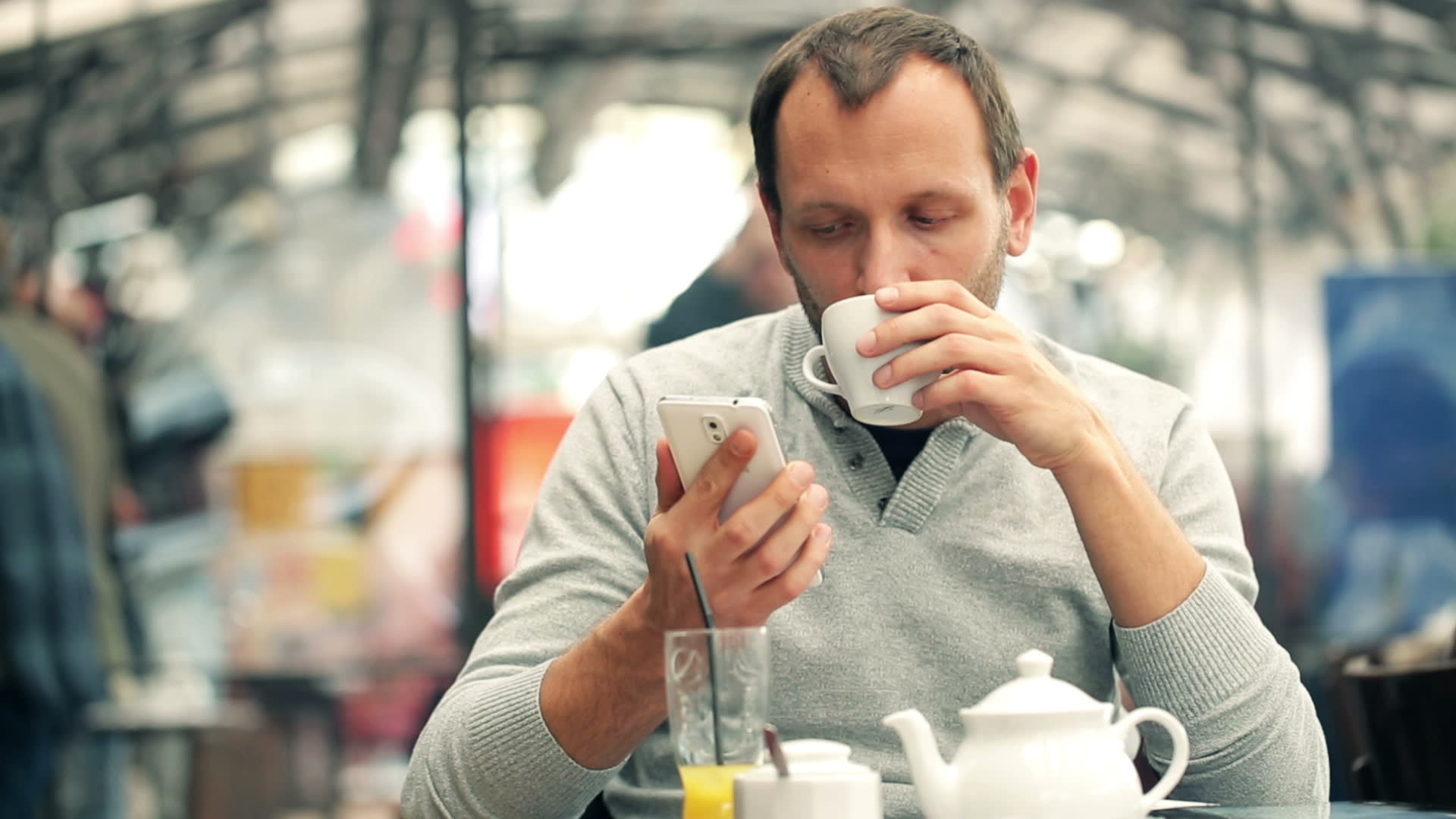 man texting on smartphone and drinking tea in cafe